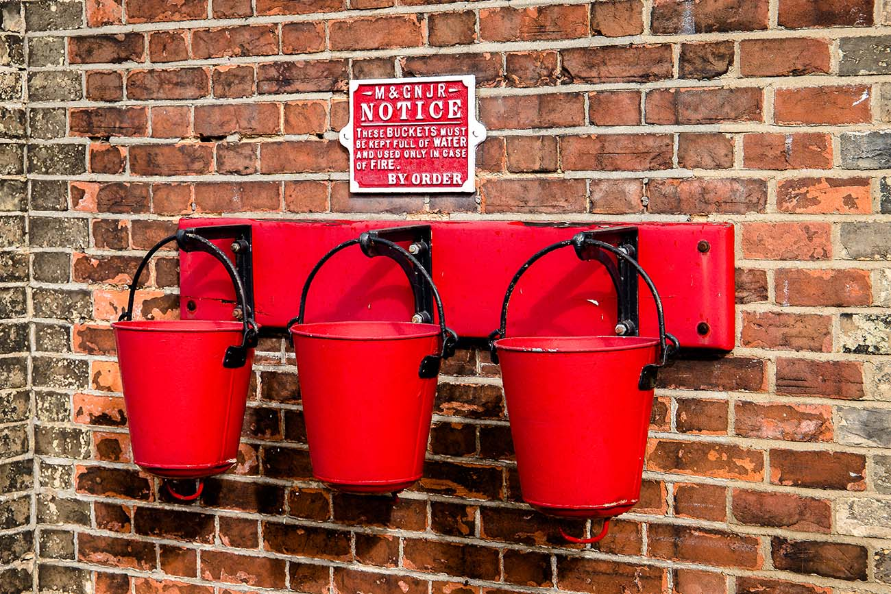 Three fire buckets hanging on the wall